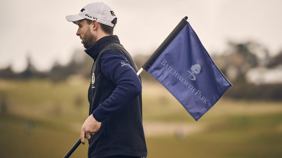 batchworth golfer holding crown golf flag