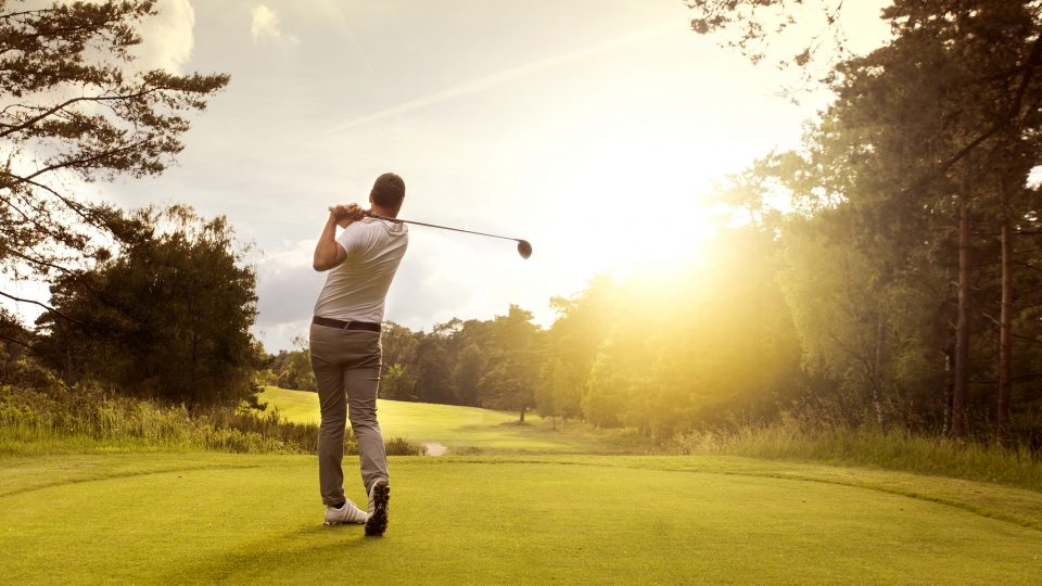 Man,Playing,Golf,On,A,Golf,Course,In,The,Sun